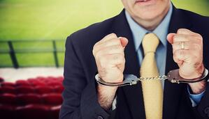 Closeup of businessman with handcuffed hands against red bleachers looking down on football pitch
