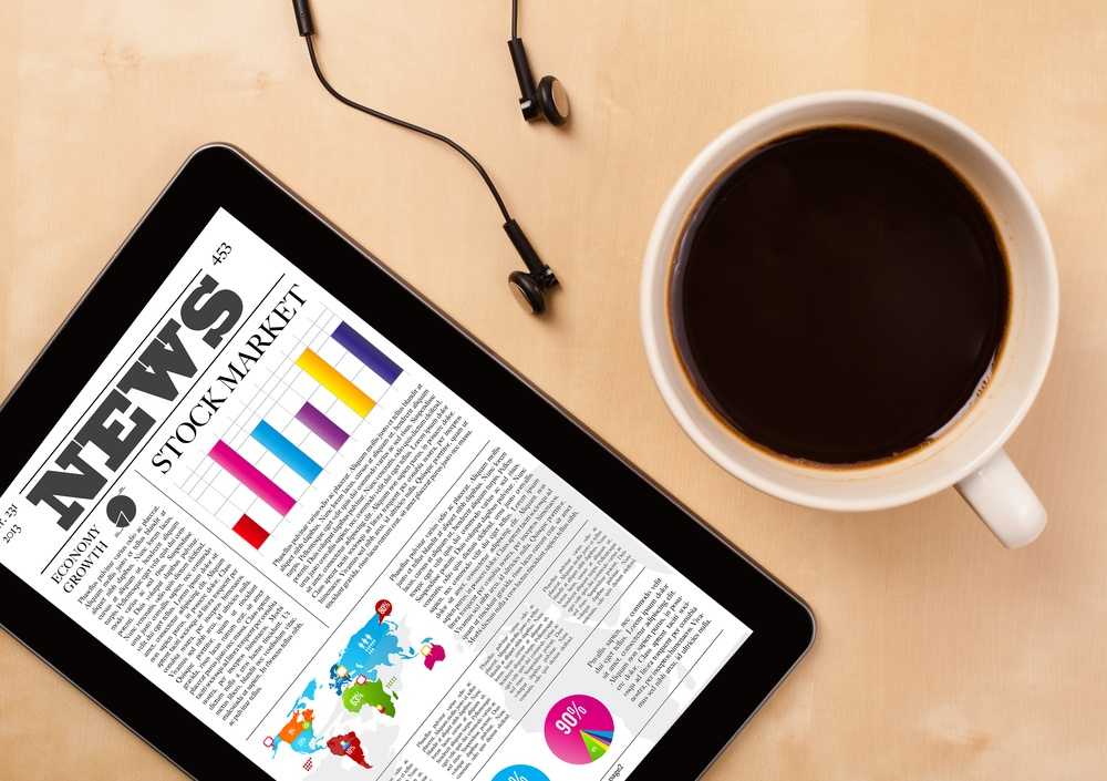 Workplace with tablet pc showing latest news and a cup of coffee on a wooden work table close-up.jpeg
